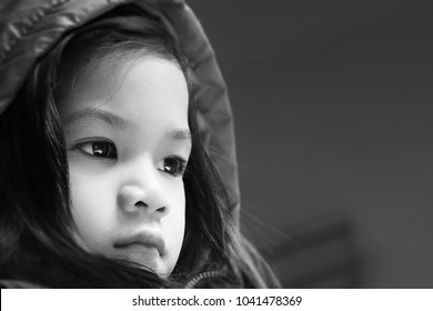 Black and white portrait of 5 year old Asian little girl.Girl look sad or scare or feel bad.Loneliness is common when kid start pre-school or big life changes.Concept of sad,lonely and in trouble kid.