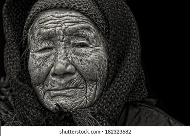 Black and white portrait of a 95 years old woman, born in 1919, with depression, the last generation that bind the feet of woman