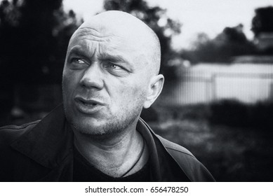Black and white portrait. The adult bald man. He is sad and unhappy. Close-up.