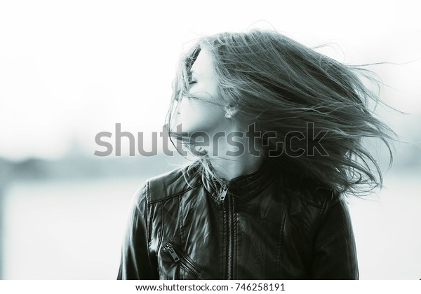 Black and white portrait of an adult girl in windy weather