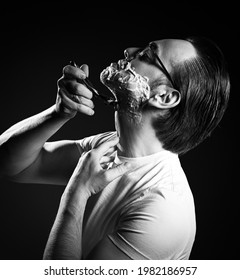 Black and white. Portrait of adult man in white t-shirt and glasses shaving with razor blades and shaving gel foam over dark background. Side view
