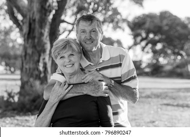 black and white portrait of American senior beautiful and happy mature couple around 70 years old showing love and affection smiling together in the park having a romantic walk relaxed enjoying