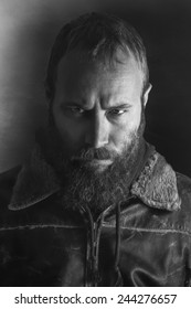 Black and white portrait of an angry bearded man.
