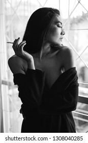Black and white portrait of asian woman with cigarette.