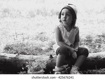 black and white portrait of a baby sitting on a log