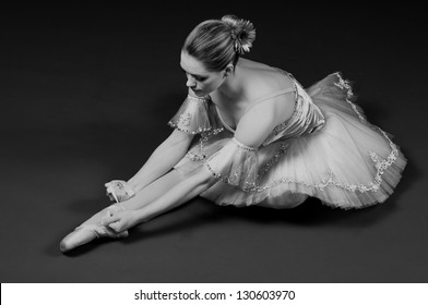 Black and white portrait of ballerina tying up pointe shoes