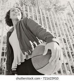 Black and white portrait of beautiful african american teenager girl holding a basketball in urban sports court, smiling outdoors. Black female young woman, sports activities recreation lifestyle.