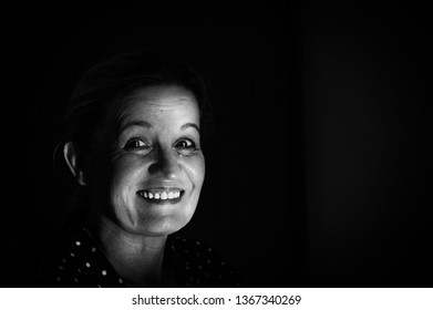 Black and white portrait of a beautiful Caucasian mature woman in 60s in a room.