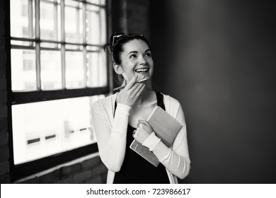 Black and white portrait of beautiful Caucasian young brunette woman. Student female drawing designer artist in hall of college university. Person at work, business situation. Hobby job concept
