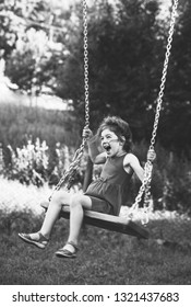 Black and white portrait of Beautiful little girl smiling on swing at summer day, Happy childhood concept. Soft focused.