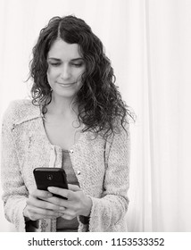 Black and white portrait of beautiful professional female holding using smartphone, indoors. Business woman with technology, telecommunications mobile phone connectivity lifestyle.
