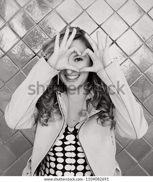 Black and white portrait of beautiful retro young woman looking smiling making heart shape with hands, americana style, outdoors. Vintage female love symbol, fun playful lifestyle leisure.
