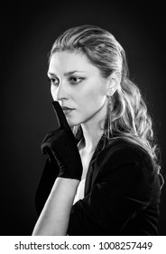 Black and white portrait of beautiful serious woman in black gloves holding finger near lips in keep silence or shush gesture. Secret concept.