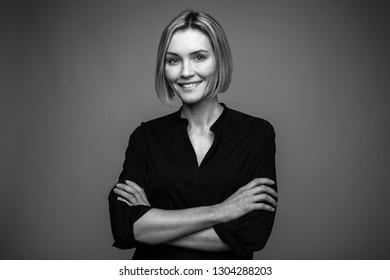 Black and white portrait of a beautiful smiling woman on a dark background