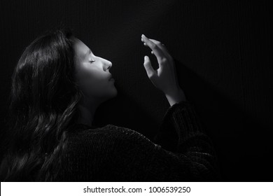 Black and white portrait of beautiful woman with a beam of light on her face