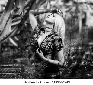 Black and white portrait of a beautiful woman with punk make up and outfit with blonde hair posing in an abandoned green house where nature has taken its toll