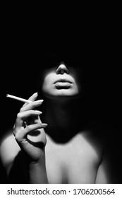 Schwarz-Weiß-Portrait von Schöne Frau in einem Hut und mit einer Zigarette. Retro-Portrait. Lady Girl mit Gesicht unter Schatten