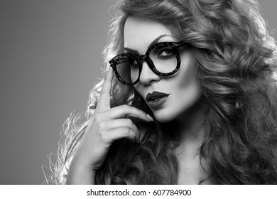 Black and white portrait of a beautiful woman in glasses