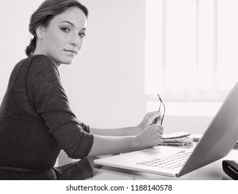 Black and white portrait of beautiful young professional woman at office desk with laptop computer, holding glasses looking indoors. Businesswoman at work using technology, lifestyle.