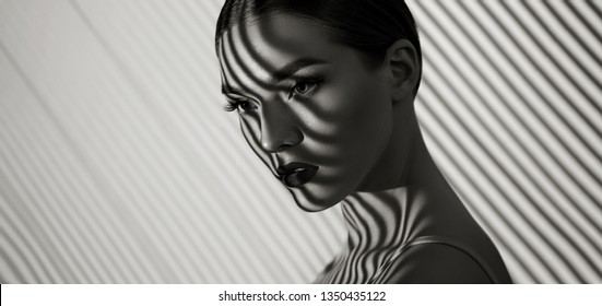 Black and white portrait of a beautiful young girl with a shadow pattern on the face and body in the form of stripes.fashion, beauty, makeup, cosmetics, beauty salon, style, personal care, posture.