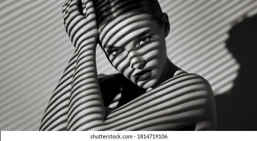 Schwarz-Weiß-Porträt einer schönen jungen Frau mit einem Schattenmuster auf dem Gesicht und Körper in Form von Streifen.