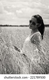 black and white portrait of a beautiful young woman in the summer field