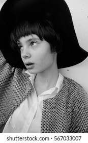 black and white portrait of a beautiful young girl with short hair in a hat near a white wall, fashion