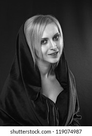 black and white portrait of blond woman with head covered with black fabric
