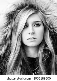Black and white portrait of blonde girl with long natural hair wearing black coat with fur hood