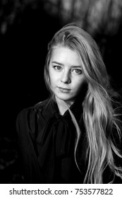 black and white portrait of a blonde at night. A thoughtful playful look