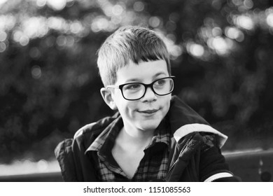 Black and white portrait of a boy with glasses outside.