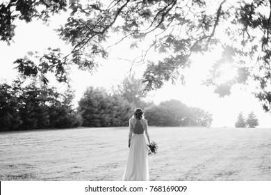 Schwarz-Weiß-Porträt einer Braut, die bei Sonnenuntergang auf dem Feld steht