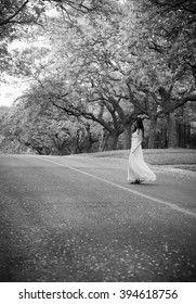 Black and white portrait of brunette girl in floaty dress dancing in a street.