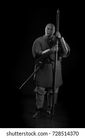 black and white portrait of a brutal bald-headed viking in battle mail with a battle ax in hands posing against a black background. Early medieval period.