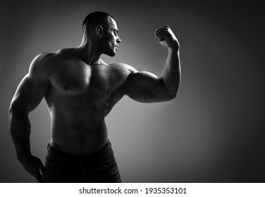 Black and white portrait of brutal strong man athlete in jeans and half naked shirtless standing showing strong huge pumped up biceps over grey background. Sport men body concept