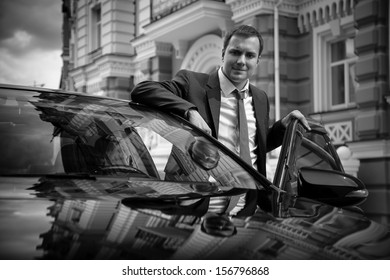 Black and white portrait of businessman standing near car