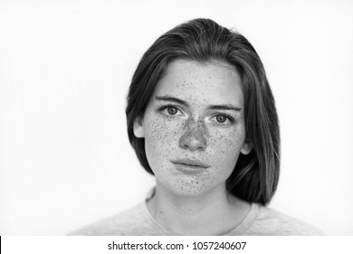 Black and white portrait of a calm and gentle beautiful girl with freckles on her face looking into the camera isolated on white background. Woman with freckles