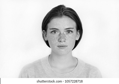 Black and white portrait of a calm and naive beautiful girl with freckles on her face looking happy in the camera isolated on white background. Positive and happy concept.