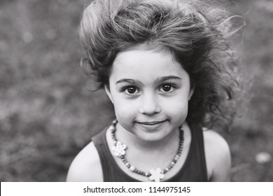 Black and white Portrait of cute little girl smiling outside