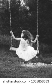 Black and white portrait of cute little girl smiling on swing at summer day, Happy childhood concept.