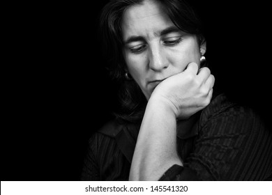 Black and white portrait of a depressed hispanic woman on a black background