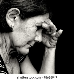 Black and white portrait of a depressed old  woman suffering from stress or a strong headache isolated on black