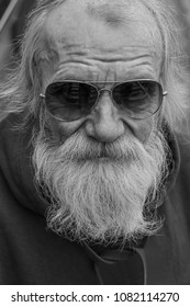 Black and white portrait of an elderly gray-haired man with a beard in a sunglasses looking at camera.