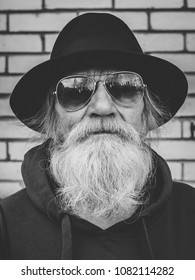 Black and white portrait of an elderly gray-haired man with a beard in a sunglasses and black hat looking at camera.