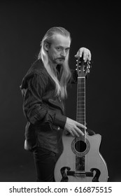 Black and white portrait of a elderly gray-haired male musician with long hair with a guitar in his hands playing and posing on a black background