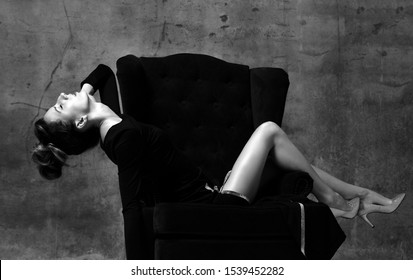 Black and white portrait of excited woman sitting across the luxury armchair with her head thrown back, sexy touching, enjoying herself on dark concrete wall background