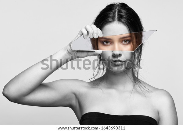 Black and white portrait of female with mirror shard in hand posing on gray background. Girl covers her face with a shard of the mirror. Eyes reflection in mirror splinter