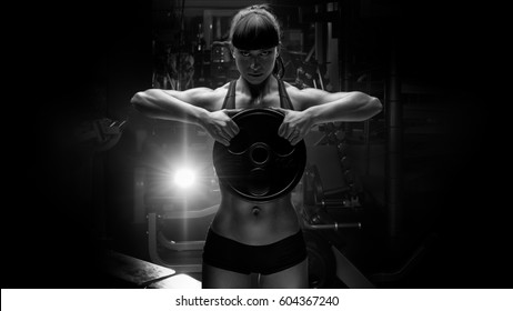 Black and white portrait of fit power athletic confident young woman trainer doing exercises with heavy weight barbell plate in gym rising hand Pumping up muscles