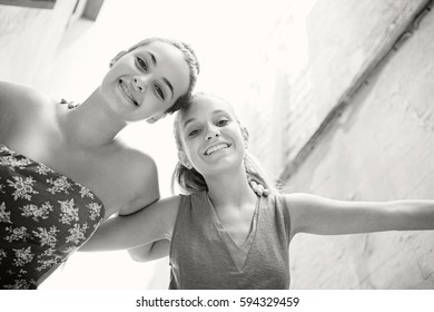Black and white portrait of fun teenager girls friends joyfully smiling looking at camera together, visiting old monument on school trip, outdoors. Travel recreation lifestyle, destination city.