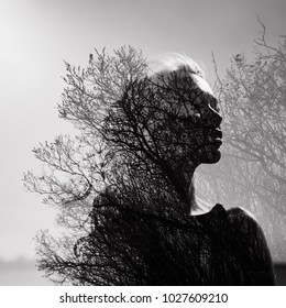 Black and white Portrait of a girl with a double exposure on a background of tree crowns. Delicate mysterious portrait of a woman against the sky